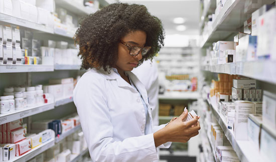 Pharmacist looking at prescription bottle